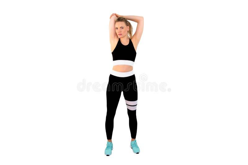 Roupa vestindo dos esportes da mulher loura 'sexy' e magro que levanta na terra traseira branca - imagem fotos de stock