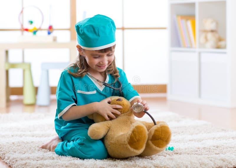 Roupa weared criança do doutor que joga com urso de peluche foto de stock
