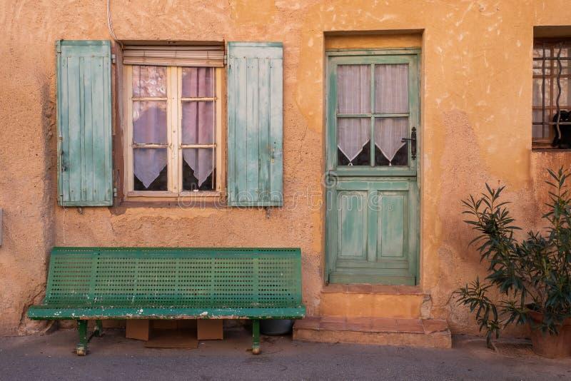 Roussillon, Frankrijk: detail van een huisvoorgevel met oker gekleurde muur en groene vensters royalty-vrije stock foto's