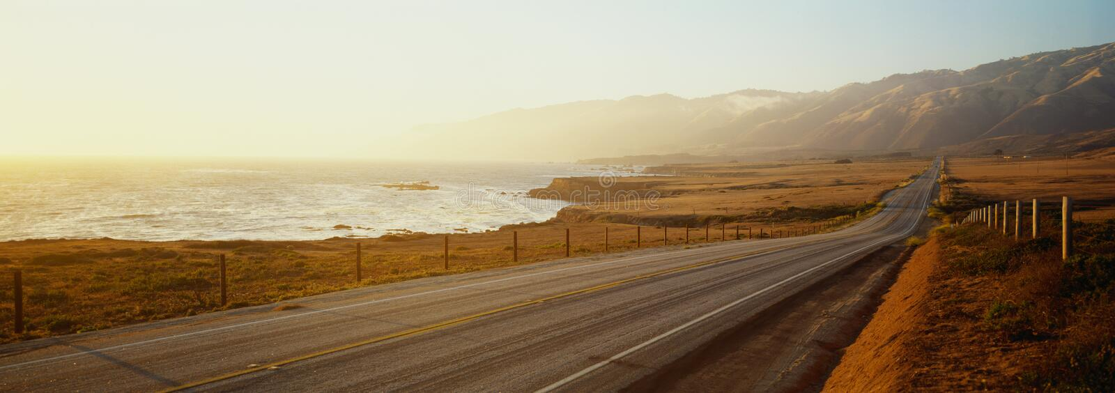 This is Route 1also known as the Pacific Coast Highway. The road is situated next to the ocean with the mountains in the. Distance. The road goes off into stock image