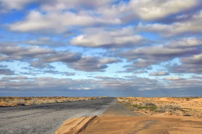 Route au coucher du soleil traversant le désert de Karakum au Turkménistan photographie stock libre de droits