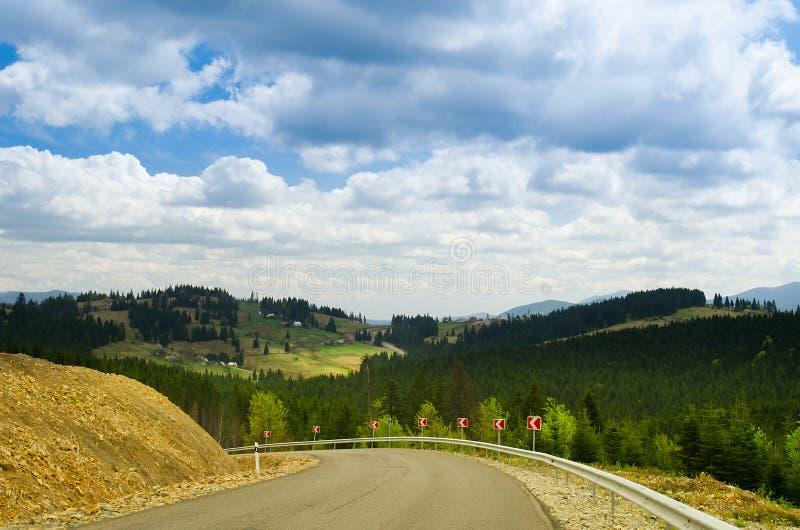 Route avec des indicateurs en montagne de forêt Carpathien, Ukraine photographie stock