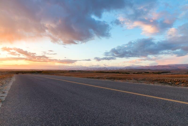 Route avec la lueur de coucher du soleil image stock