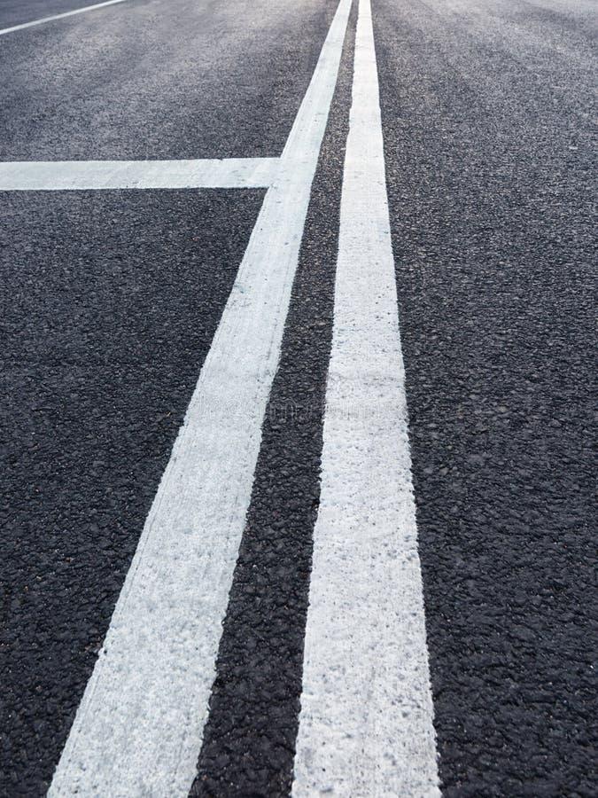 Route avec la perspective de diminution d'inscription blanche images stock