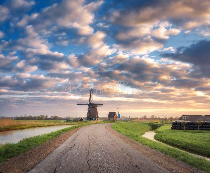 Route avec le moulin à vent au lever de soleil aux Pays-Bas photos stock