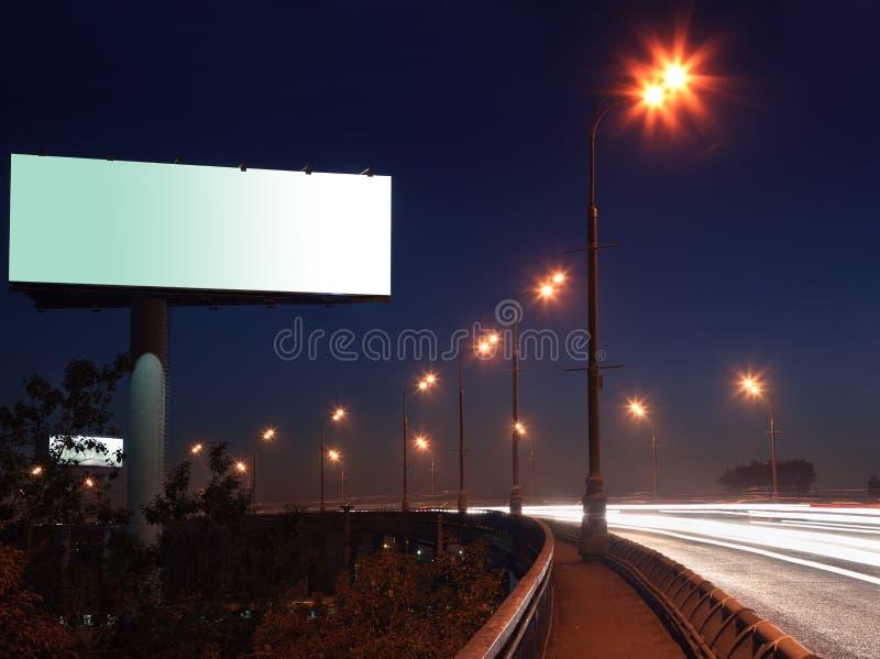 Route avec les lumières et le grand panneau-réclame blanc images stock