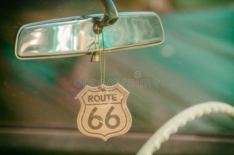 Route 66 badge hanging on a car mirror. Of a classic car royalty free stock photo
