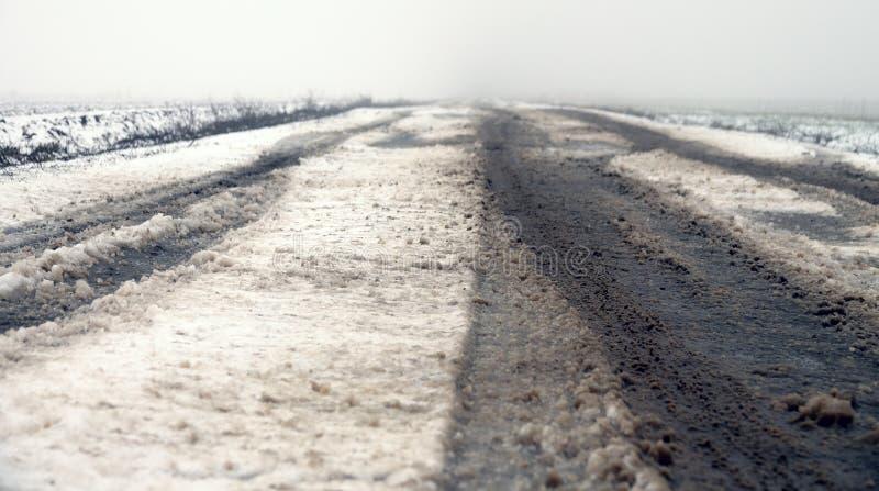 Route brumeuse d'hiver parmi des champs en d?cembre images libres de droits