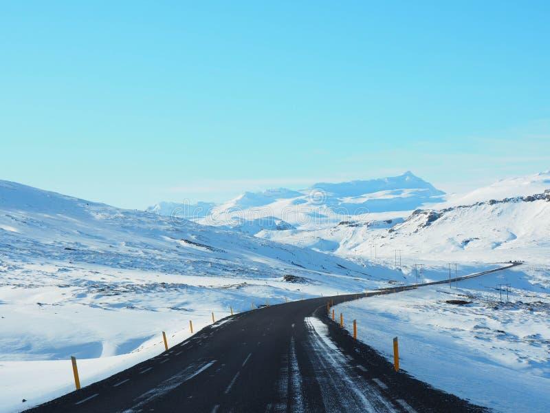 Route d'hiver avec la montagne du côté de la route couverte de s images stock