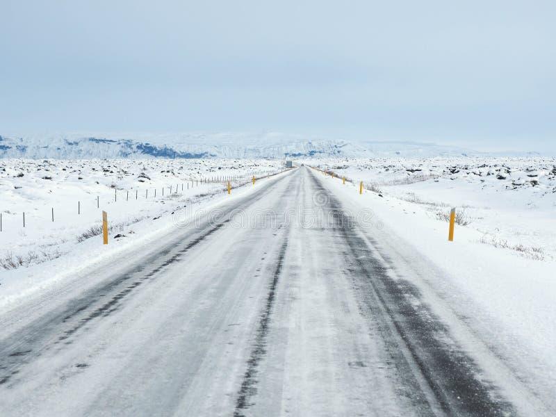 Route d'hiver avec la montagne du côté de la route couverte de s images libres de droits