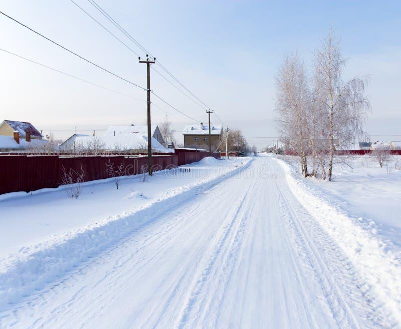 Route dans la neige dans le village photographie stock libre de droits