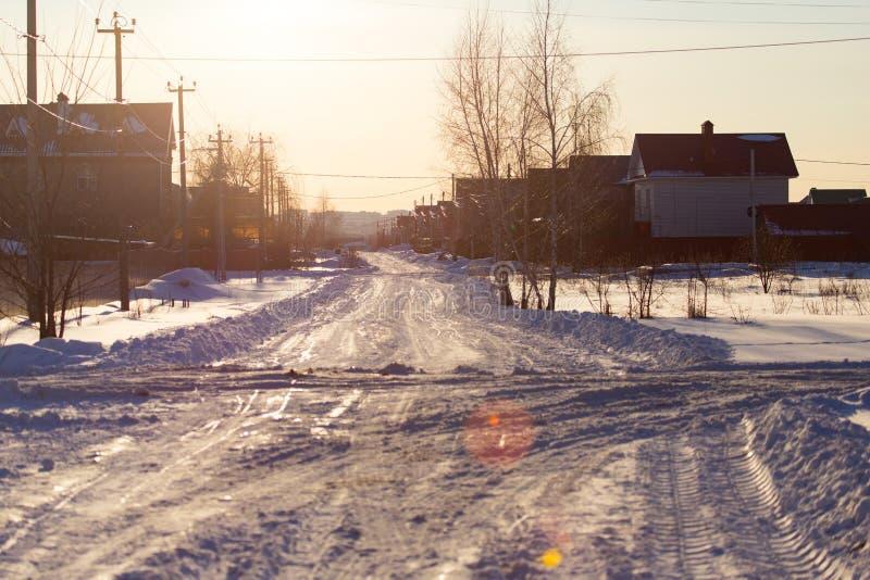 Route dans la neige dans le village au coucher du soleil image libre de droits