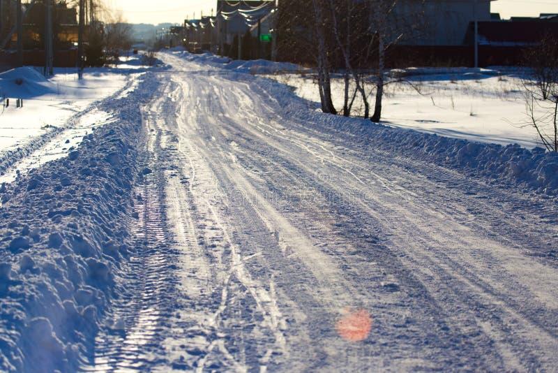 Route dans la neige dans le village au coucher du soleil image stock