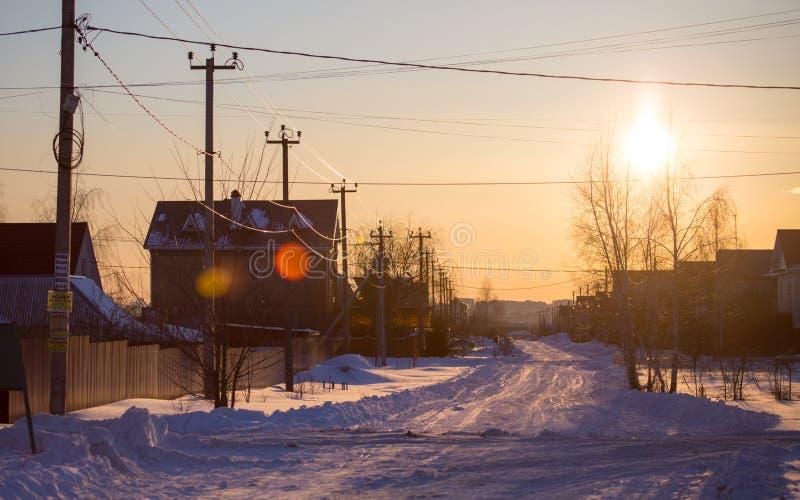 Route dans la neige dans le village au coucher du soleil images libres de droits