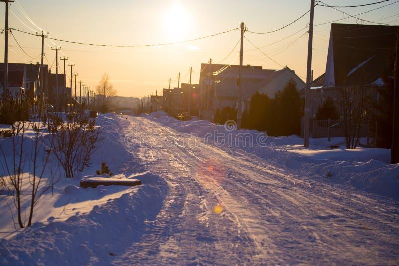 Route dans la neige dans le village au coucher du soleil photo stock