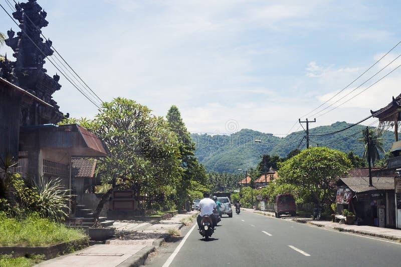 Route dans le village avec conduire des voitures et des personnes photos stock