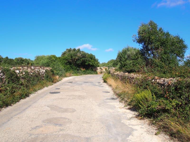 Route de campagne étroite typique dans le menorca entourée par de vieux murs de pierres sèches avec les champs environnants et ar photos stock