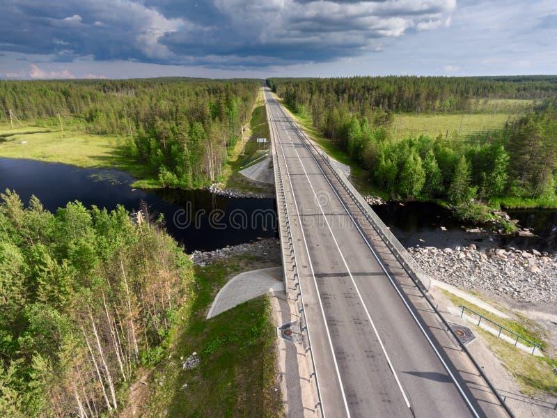 Route de campagne d'asphalte à travers la petite rivière Pont au-dessus de l'eau et des marais La Carélie, Russie photo libre de droits