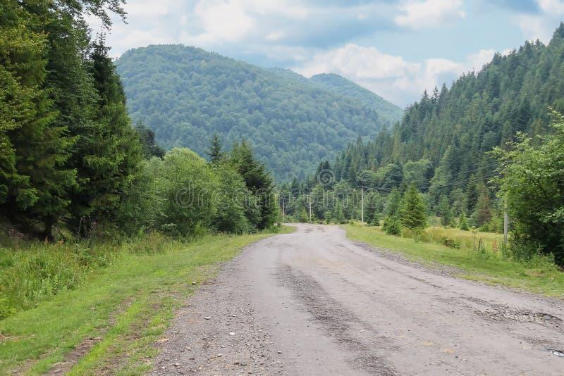 Route de campagne entre de petits règlements dans les Carpathiens photos stock
