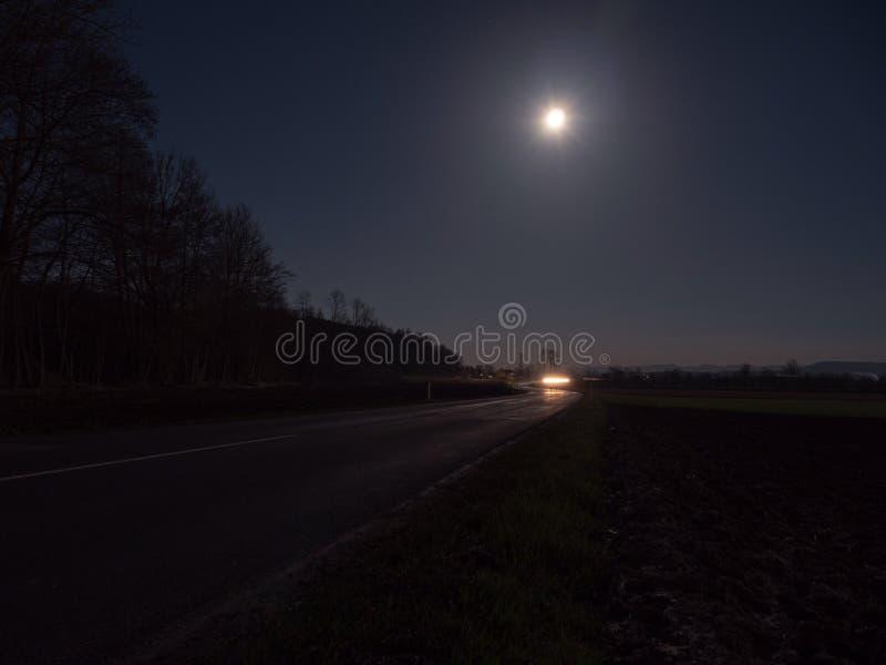 Route de campagne illuminée par les phares d'une voiture de approche photo libre de droits