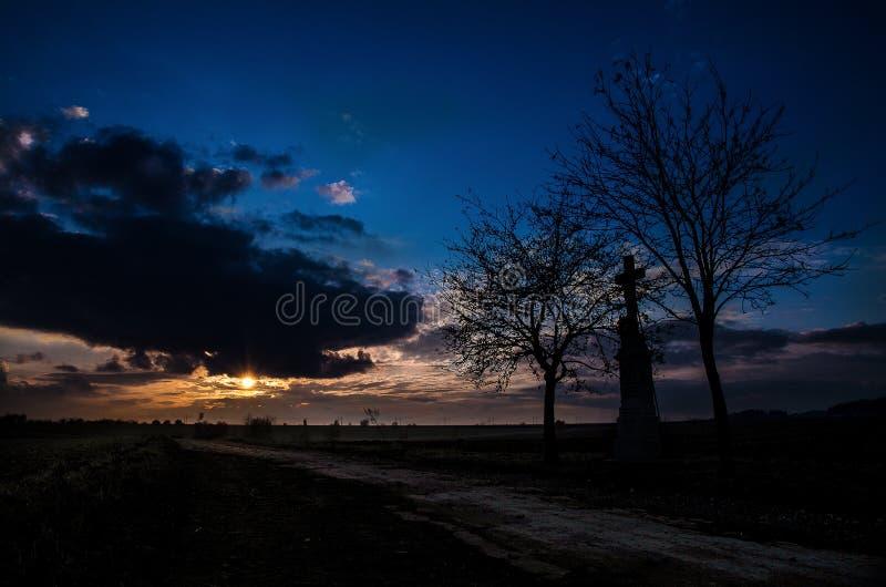 Route de ciel d'arbre et de croix de coucher du soleil photo stock