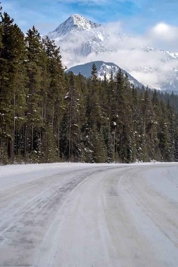 Route de route express de vallée d'arc couverte dans la glace et la neige de montagne de cascade à l'arrière-plan pendant l'hiver image stock