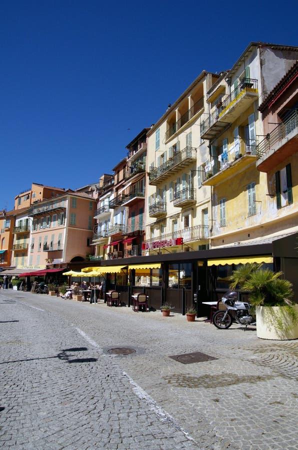 Route de macadam avec des maisons et des restaurants dans Villefranche Sur Meer dans les Frances images stock
