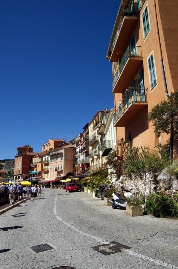Route de macadam avec des maisons et des restaurants dans Villefranche Sur Meer dans les Frances photo libre de droits