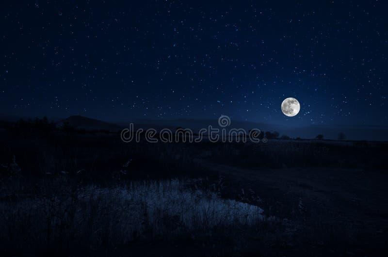 Route de montagne par la forêt une nuit de pleine lune Paysage scénique de nuit de route de campagne la nuit avec la grande lune  photo stock