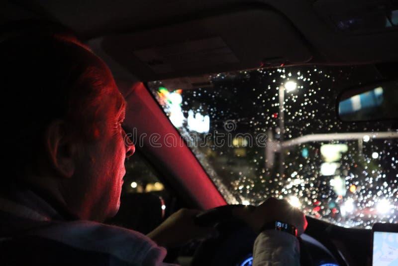 Route de nuit Vue de l'intérieur de voiture Lumière normale l'homme conduisant une voiture la nuit dans le visage reflète la coul photos stock