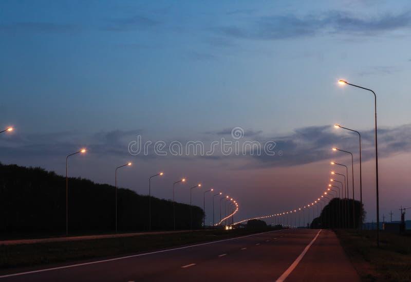 Route de soirée avec les lanternes lumineuses La route entre dans la distance images libres de droits