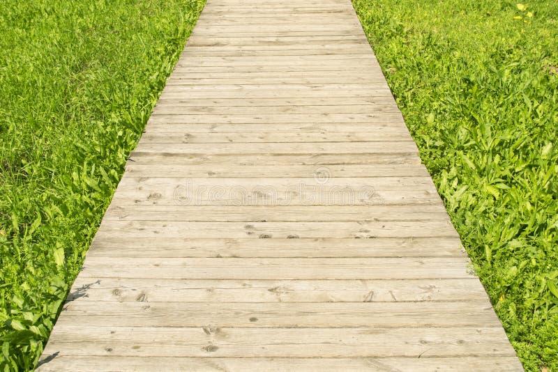 Route en bois par l'herbe photo stock