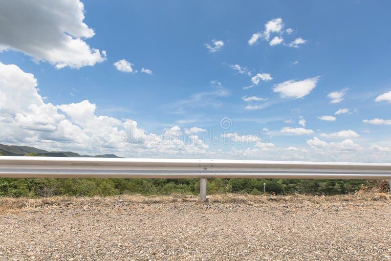 Route et barrière à avec le fond de ciel bleu et raincloud se déplaçant à la lumière du soleil d'après-midi photographie stock libre de droits