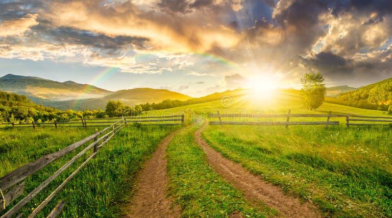 Route et barrière en bois sur le flanc de coteau au coucher du soleil image stock