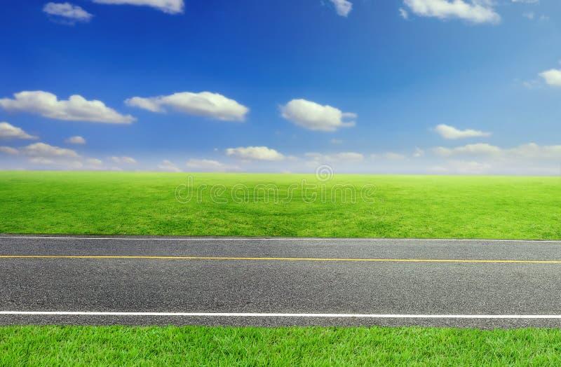 Route et herbe de ciel et verte nuageuse images stock