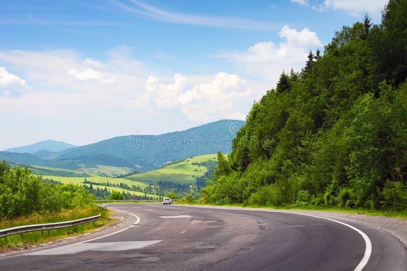 Route et voiture incurvées en montagnes photo stock