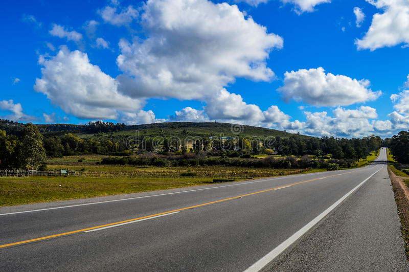 Route 9. Excerpt from Route 9 in Uruguay, surrounded by trees and vegetation showing blue sky with clouds stock images