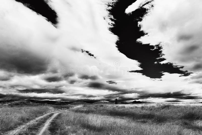 Route going to horizon black and white. Rural landscape with cart road going to far horizon and heavy rain clouds wide angle black and white stock image