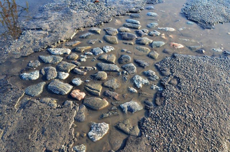 Route goudronnée cassée avec des trous et des magmas pendant le premier ressort photographie stock libre de droits