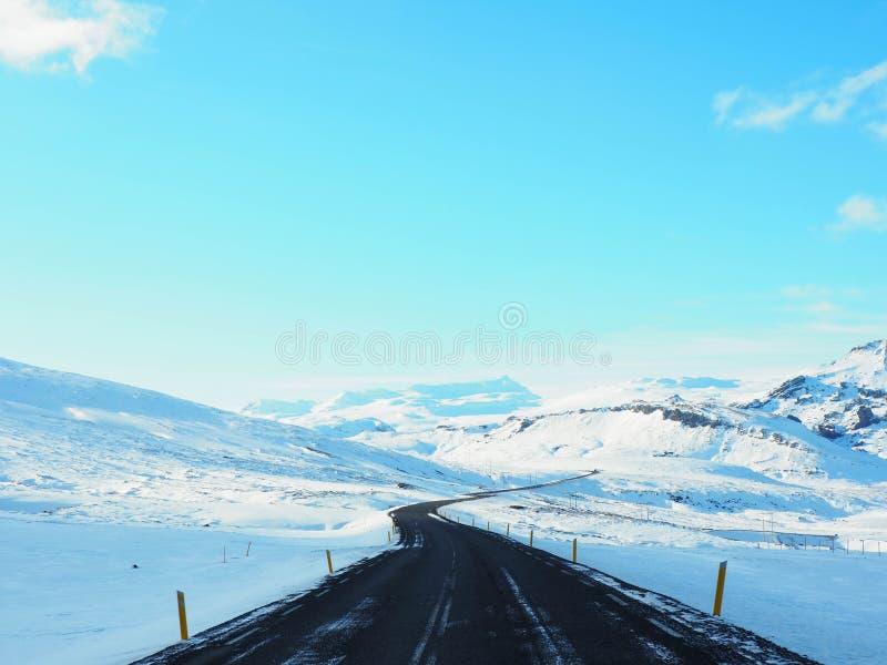 Route goudronnée incurvée d'hiver avec la montagne du côté de la route photographie stock