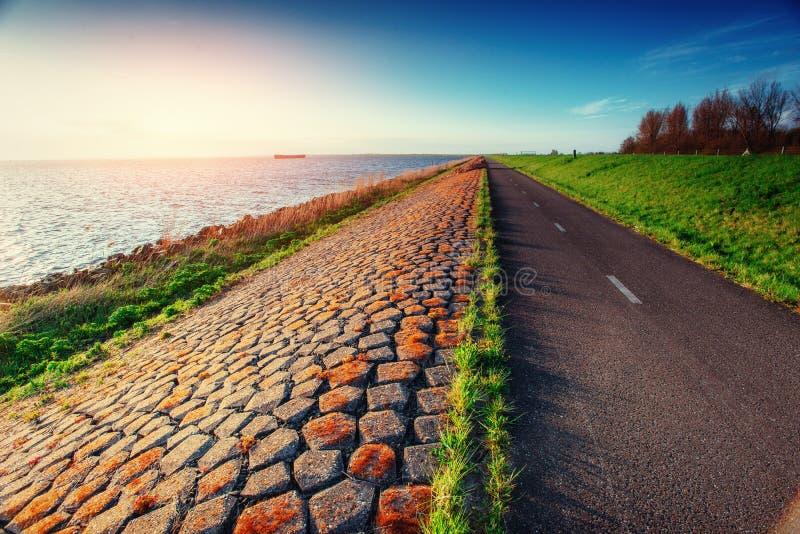 Route goudronnée le long de la mer au coucher du soleil image stock