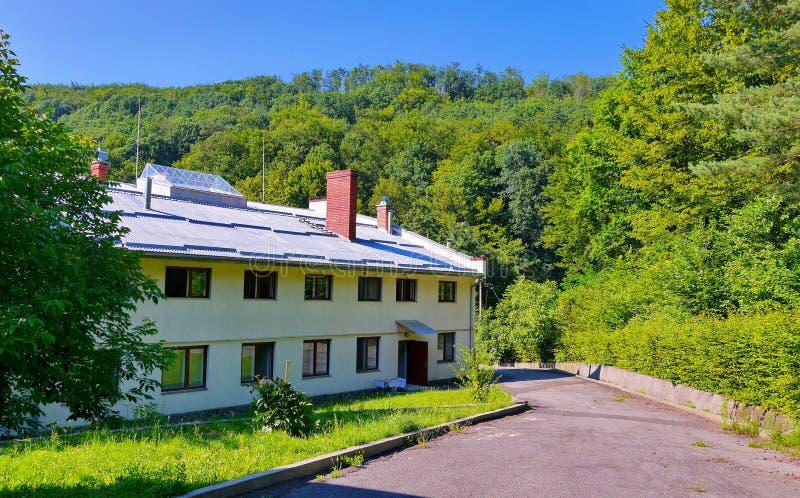 Route goudronnée menant à un bâtiment à deux étages à la nuance des arbres feuillus verts photographie stock