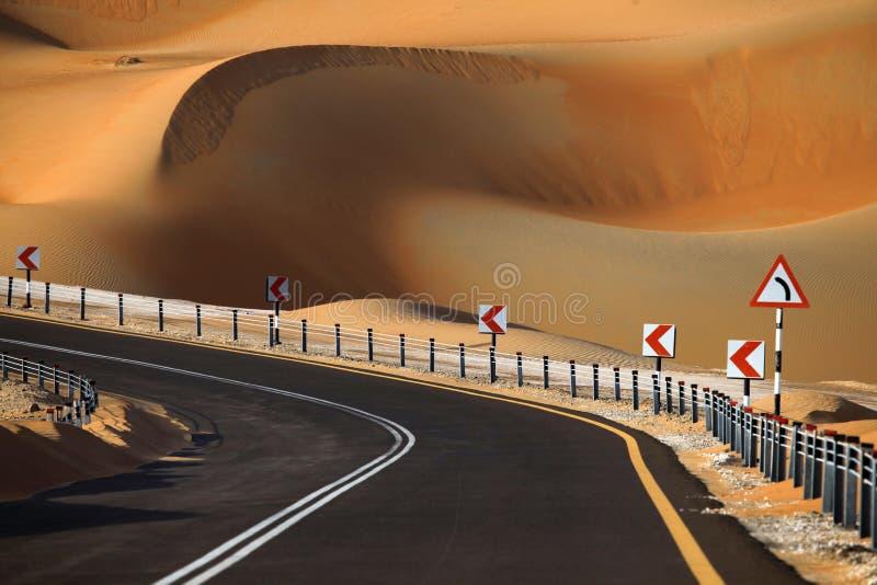 Route goudronnée noire de enroulement par les dunes de sable de l'oasis de Liwa, Emirats Arabes Unis images libres de droits