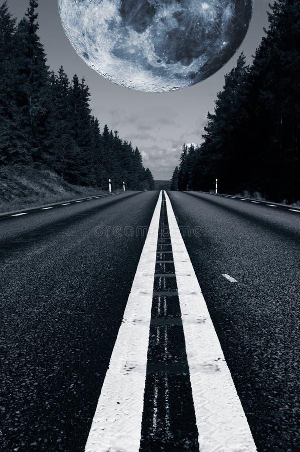 Route isolée avec une lune surréaliste géante photo stock