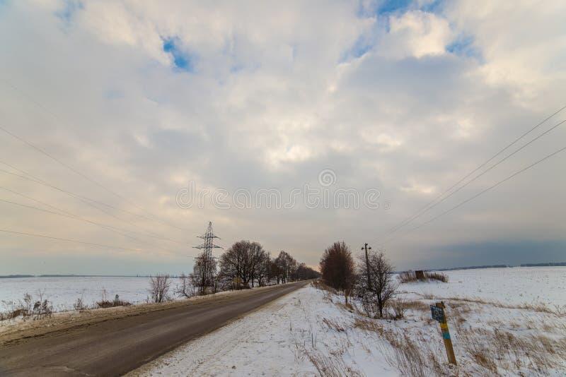 Route isolée d'hiver qui va au terme Autour de la neige nuages très beaux au coucher du soleil images libres de droits
