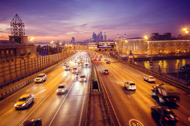 Route la nuit avec les lumières de beaucoup de voitures sur le fond de la métropole photo libre de droits