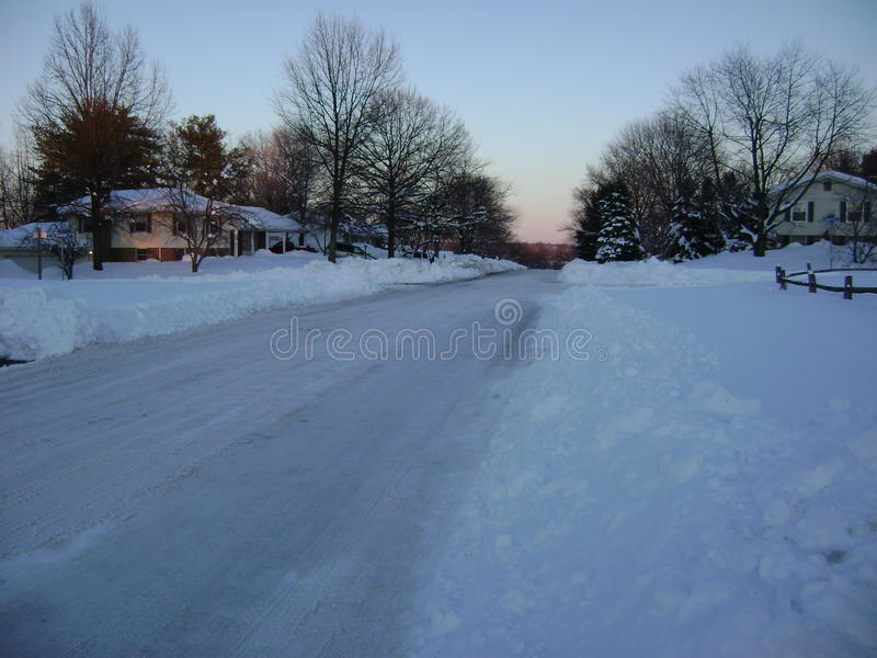 Route labourée dans la banlieue neigeuse photos stock