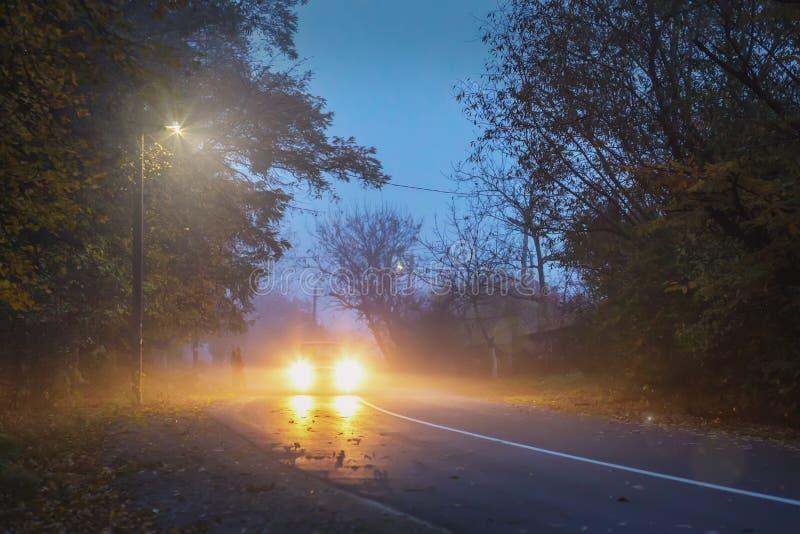 Route le soir, automne, brouillard, voiture sur la route, images libres de droits