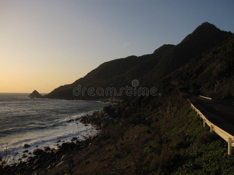 Route, montagnes et la mer pendant le coucher du soleil photos stock