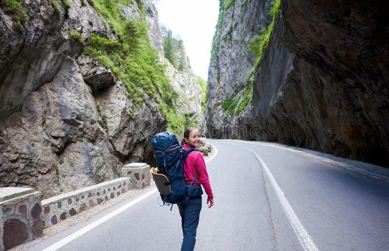 Route montagneuse vide de marche de sourire de touriste de feamle en canyon spectaculaire de Bicaz en Roumanie photographie stock